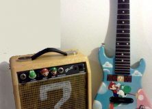 Custom painted guitar with Mario and Yoshi. Also direct your attention to the cleverly painted ? block amp.